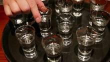 Auf einem runden schwarzen Tablett stehen Schnapsgläser mit klarer Flüssigkeit. Eine Hand hebt eines der Gläser an.