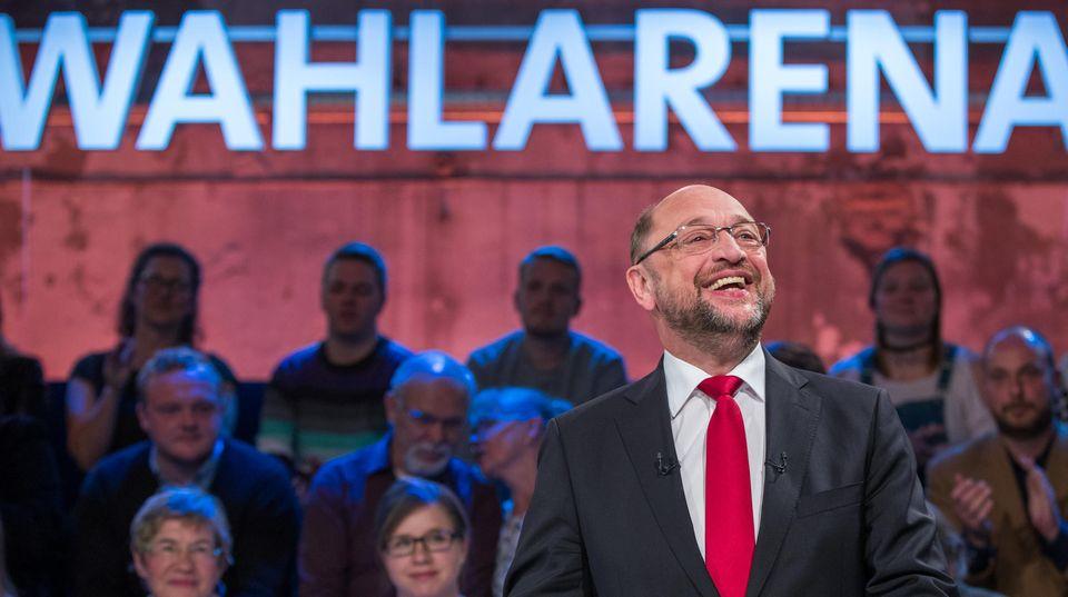 """Unter der Leuchtschrift """"Wahlarena"""" steht Martin Schulz und lacht. Er trägt eine rote Krawatte zum dunkelgrauen Anzug"""