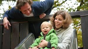 Junge Familie mit Kind auf der Spielplatz-Rutsche