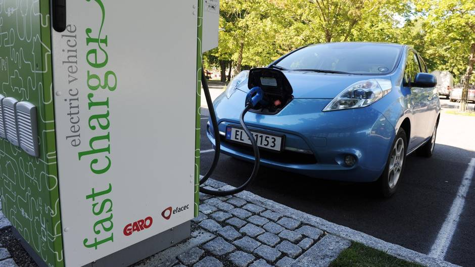 Ein Auto steht an einer Ladestation und ist zum Laden der Batterien angeschlossen