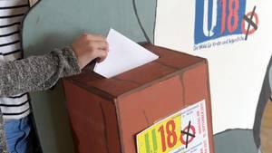 Ein Wahlumschlag wird in den U18-Wahlkasten gesteckt
