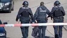 Polizeibeamte gehen in Villingendorf hinter einer Absperrung in der Nähe des Tatorts.