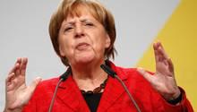 Angela Merkel mit verkniffenem Gesicht, hebt die Hände am Rednerpult