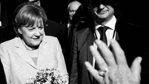 Angela Merkle wird in Kühlungsborn von einer Bürgerin begrüßt, die ihr schnell einen Strauß Blumen aus dem Garten geholt hatte
