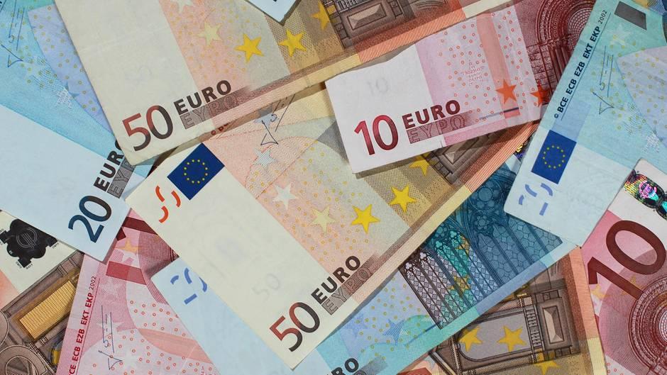 Geldscheine für 10, 20 und 50 Euro liegen ausgebreitet auf einer Fläche