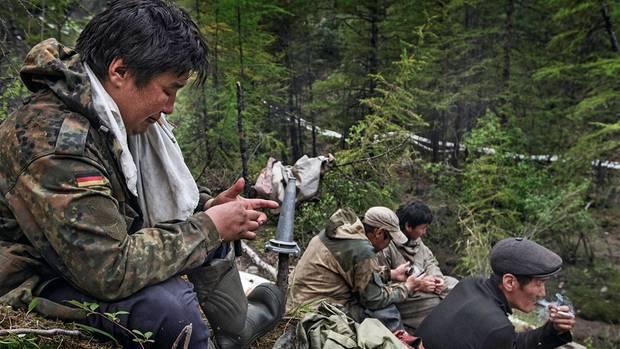 Zigarettenpause neben der Höhle. Ständig gehen Pumpen kaputt, Wassilij (l.) wartet zusammen mit anderen Arbeitern darauf, dass aus den Schläuchen wieder Wasser läuft