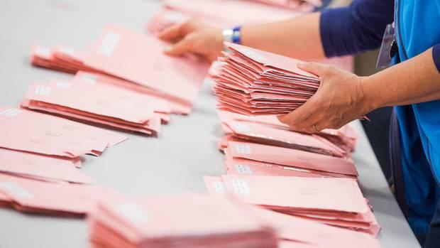 Rote Umschläge mit abgegebenen Briefwahlstimmen werden in Köln sortiert.