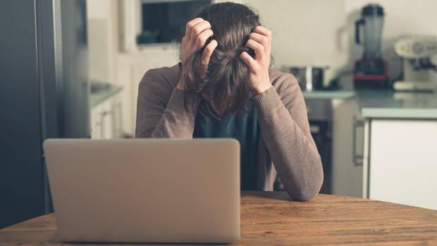 Eine Frau sitzt mit gesenktem Kopf vor ihrem Laptop und rauft sich die Haare