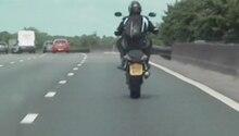 Ein Motorradfahrer macht auf der Autobahn M6 in England einen Wheelie: er fährt nur auf dem Hinterrad