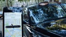 Ein Smartphone-User hat die Uber App geöffnet, im Hintergrund eins schwarzes Taxi aus London