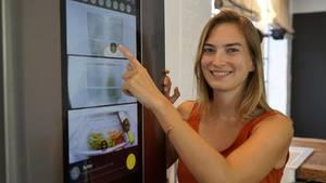 stern.de-Genuss-Redakteurin Denise Wachter vor dem vernetzten Samsung-Kühlschrank in einer smarten Küche. Das Display zeigt, was im Kühlschrank liegt.