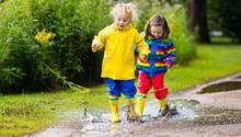Zwei Kinder hüpfen in einer Pfütze