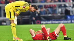 Robert Lewandowski (r.) vom FC Bayern München liegt vom VfL Wolfsburg Torwart Koen Casteels nach einem Zweikampf auf dem Boden