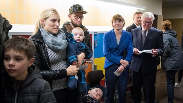 Warten auf die Stimmabgabe zur Bundestagswahl: Bundespräsident Frank-Walter Steinmeier (rechts) und seine Frau Elke Büdenbender (2. von rechts) stehen zusammen mit anderen Wahlberechtigten in ihrem Wahllokal in Berlin-Zehlendorf