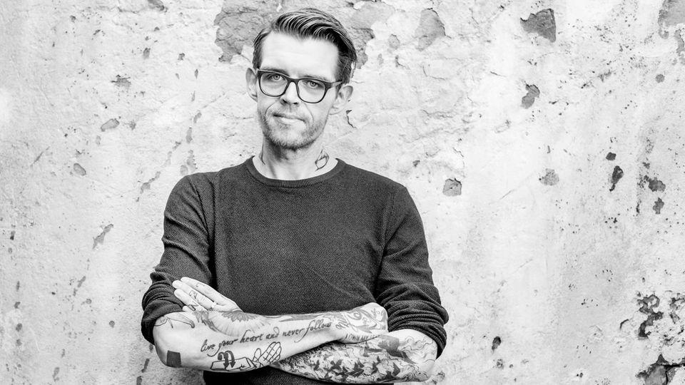 Nicholas Müller, ehemaliger Sänger der Band Jupiter Jones, steht vor einer Wand in Hamburg