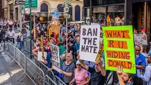Menschen protestieren an Trumps Geburtstag gegen den Einreisebann der USA in NYC