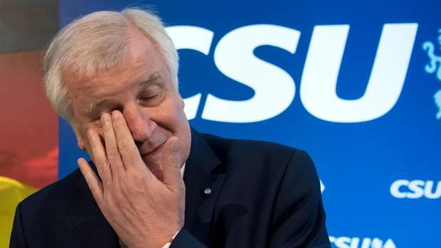 CSU-Chef Horst Seehofer reibt sich mit der linken Hand das recht Auge. Im Hintergrund eine Wand mit CSU-Logo