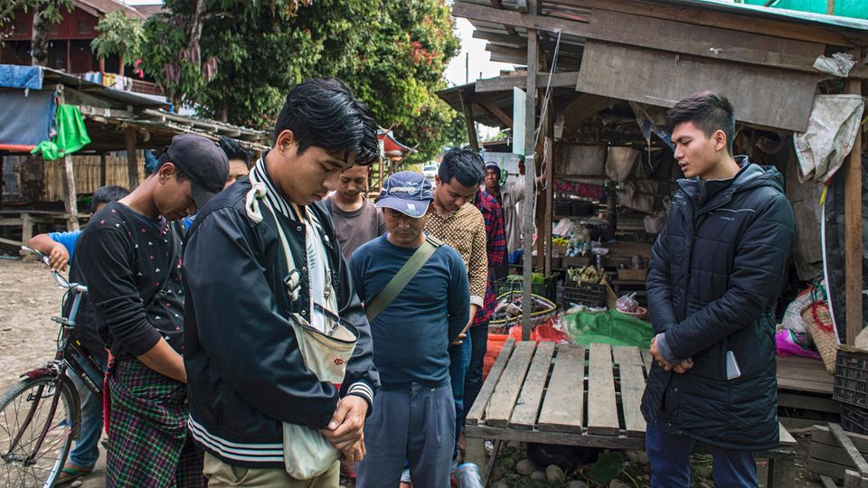 Pastor San Li, der das Bibel-Camp leitet (rechts) betet für die freiwilligen Helfer, bevor sie zu einer Razzia ausrücken.