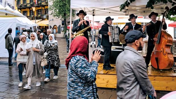 Tracht trifft Tracht: junge Araberinnen neben einer Volksmusikkapelle auf dem Stadtplatz von Zell