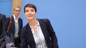 Lächelnd steht Frauke Petry auf der Bühne der Bundespressekonferenz an, hinter ihr geht AfD-Spitzenkandidatin Alice Weidel