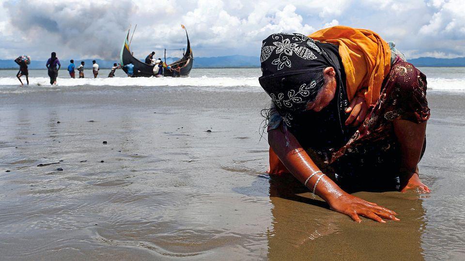 Erschöpft, aber in Sicherheit: Eine Flüchtlingsfrau berührt den Strand des Grenzflusses Naf