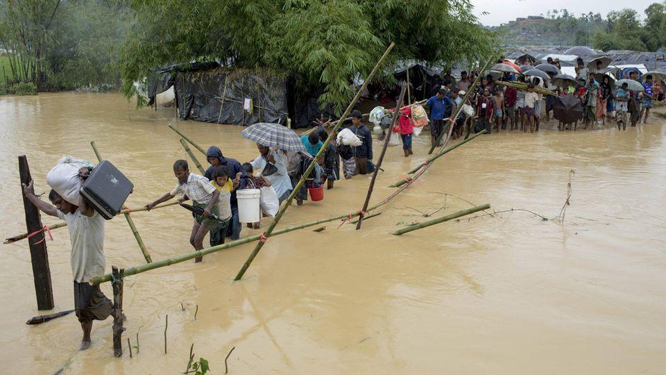 Eine Schlange, kein Ende: Entlang einer Holzkonstruktion überqueren Flüchtlinge den Fluss