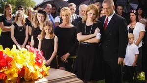 Eine Trauergemeinde steht vor einem mit Blumen dekorierten Sarg