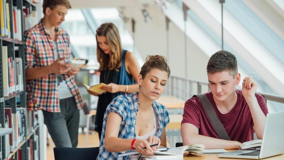 Vier junge Studierende in der Universitätsbibliothek