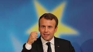 Frankreichs Präsident Emmanuel Macron ballte Faust. Ein gelber Stern auf blauem Grund umgibt seien Kopf