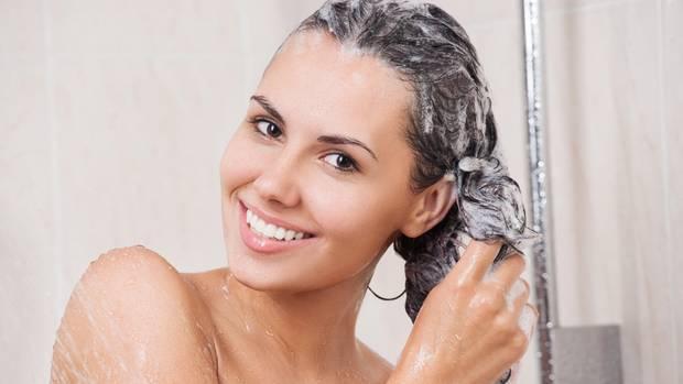 Eine Frau wäscht sich die Haare mit Shampoo.