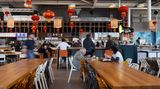 Tafeln an langen Tischen in der Bang Bang Oriental Foodhall: Wenn der Beeper blinkt und vibriert, den man bei der Bestellung erhält, kann das frisch zubereitete Essen abgeholt werden.