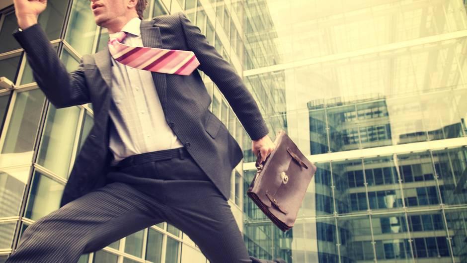 Ein Mann rennt mit Aktentasche aus einer großen Firma