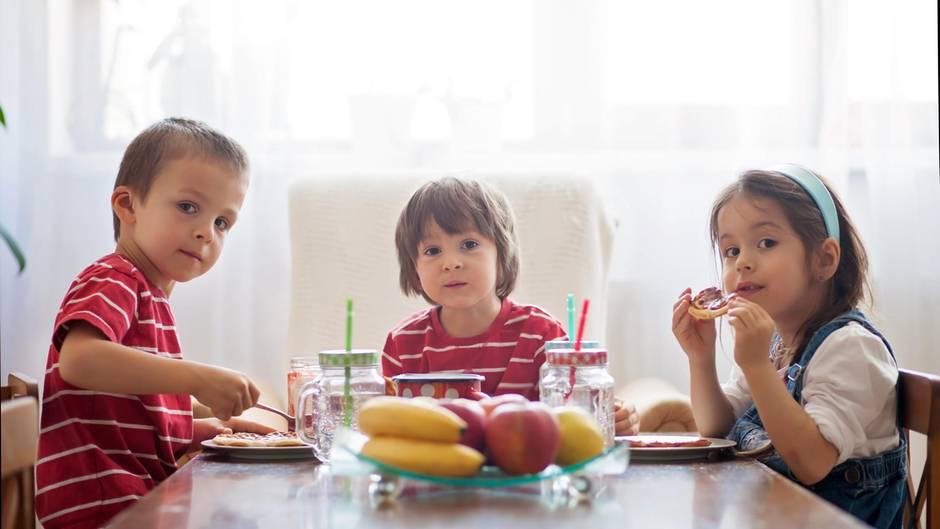 Drei Kinder am Frühstückstisch