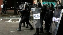 Ein spanischer Polizist zielt mit einem Gewehr für Gummigeschosse auf Befürworter des Referendums