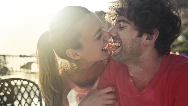 Verliebte Mann und Frau knabbern an einem Tintenfischring
