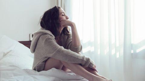 Frau sitzt nachdenklich im Bett