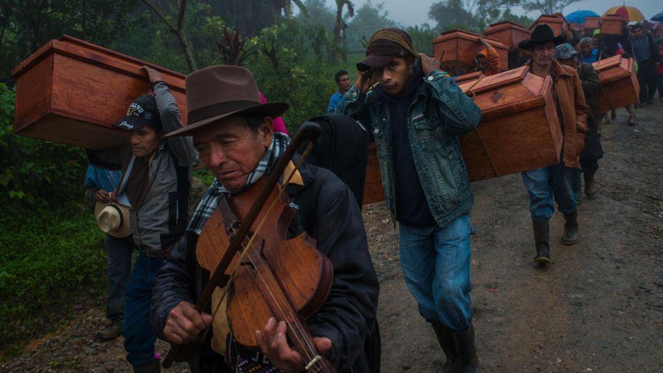 Junge und alte Männer tragen Särge mit den Überresten von Ermordeten zur Beerdigung