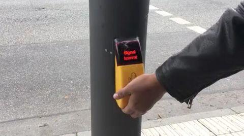 Eine Hand betätigt eine Ampel