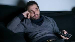 Ein Mann sitzt gelangweilt auf der Couch vorm Fernseher – ist er auch serienmüde?