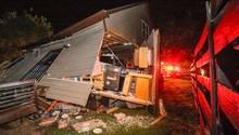Feuerwehrleute stehen vor dem Haus, das von einem entgleisten Güterzug stark beschädigt wurde