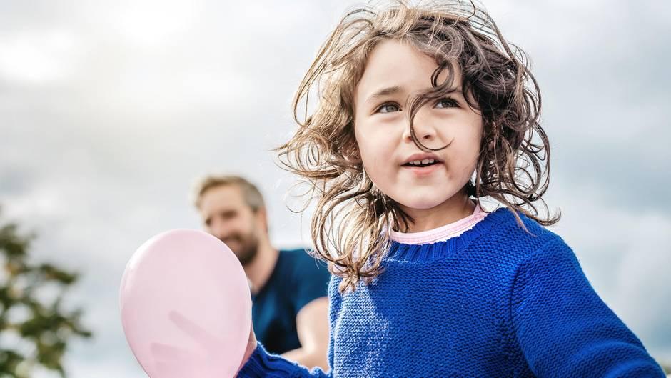 Mädchen mit rosa Luftballon schaut besorgt