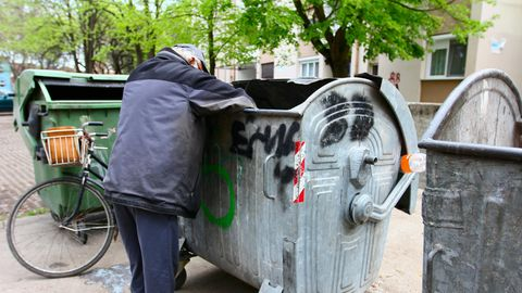 Obdachloser durchsucht Müllcontainer