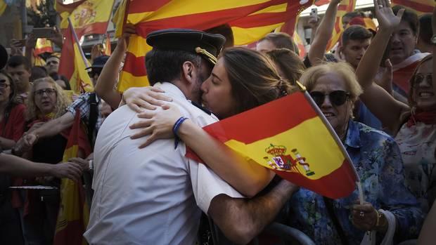 Eine Frau umarmt in Barcelona einen Polizisten der Guardia Civil