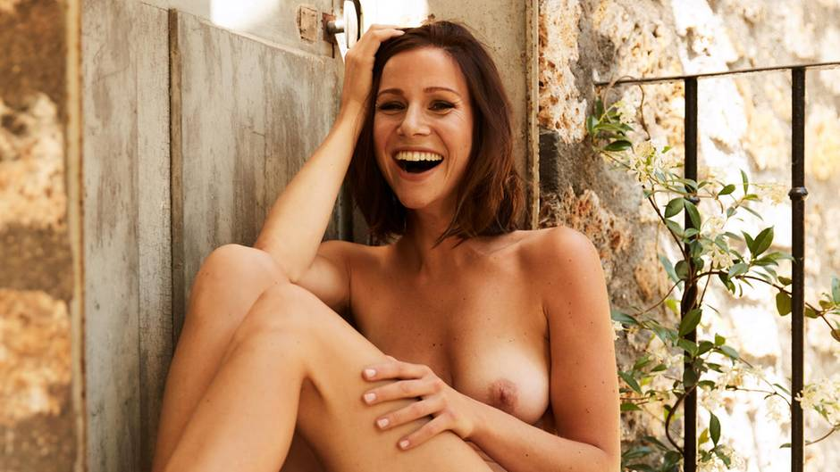 Nur mit einem Tuch um die Hüften sitzt Schauspielerin Kathrin Heß nackt auf einer steinernen Türschwelle und lacht