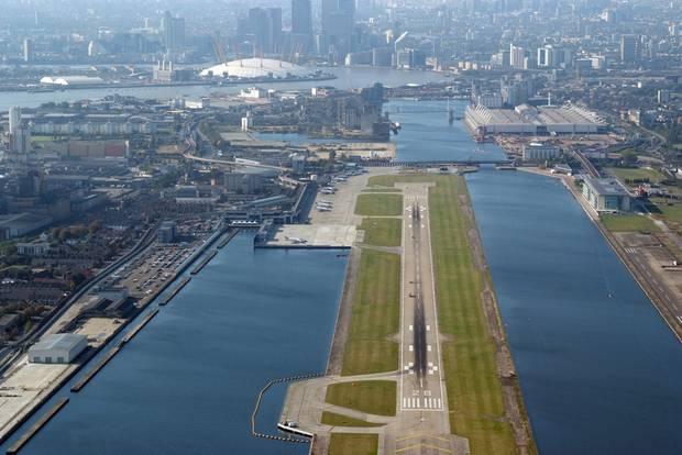 Die nur 1500 Meter lange Betonpiste im Hafenbecken. Im Hintergrund rechts die Ausstellungshallen der Messe ExCel und die weiße Kuppel des Millennium Dome an der Themse-Schleife.