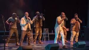 """Die Mitglieder von """"Naturally 7"""" stehen auf der Bühne und singen"""