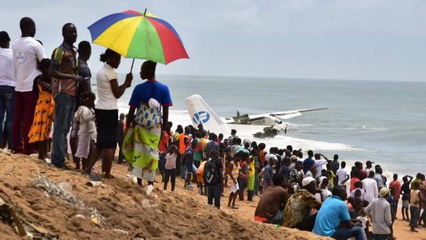 Schaulustige stehen am Strand von Port-Bouet in Abidjan und beobachten die Bergungsarbeiten