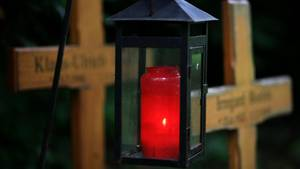 Ein Grablicht leuchtet zwischen zwei Holzkreuzen: Immer weniger Menschen entscheiden sich für Erd-Bestattungen