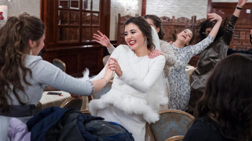 Bassy Schmukler tanzt ausgelassen im Kreis von Freundinnen und Familienmitgliedern in einem Teil des Festsaals. In dem anderen, durch einen Vorhang abgetrennten, amüsieren sich die Männer. Viel später erst kommen sie zusammen