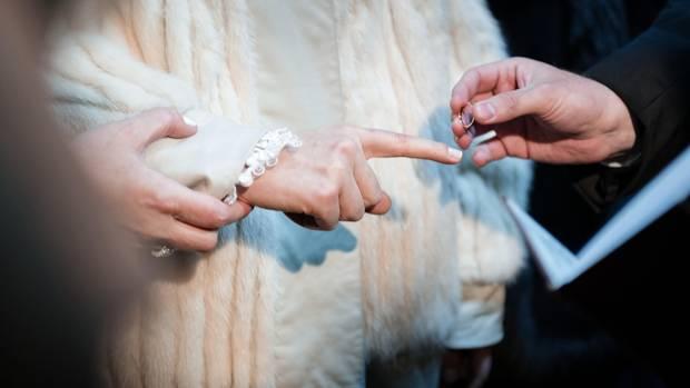 Der Bräutigam streift Bassy den Ehering über den rechten Zeigefinger